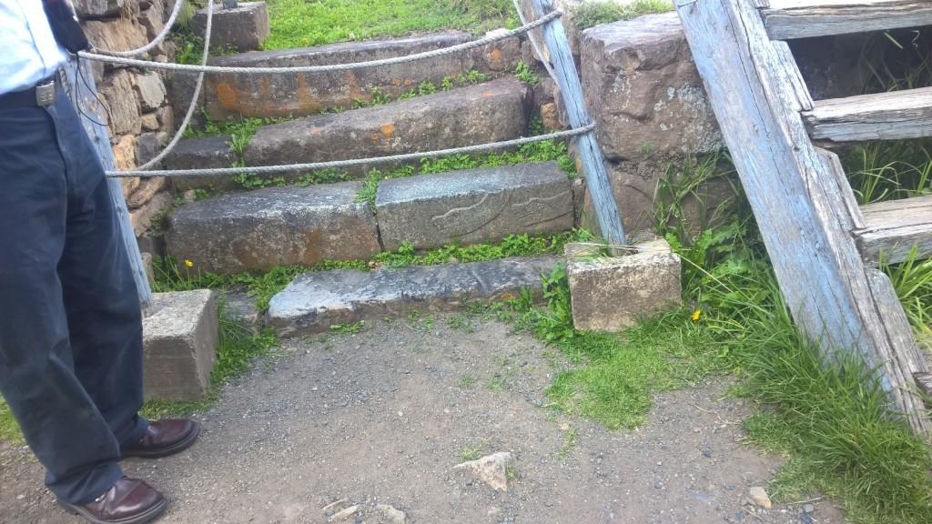 Płaskorzeźba węża na kamiennych schodach